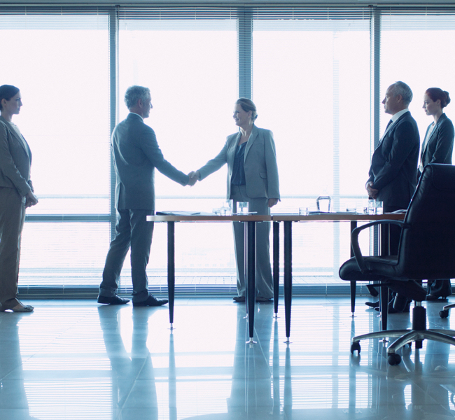 men and women shaking hands in board room