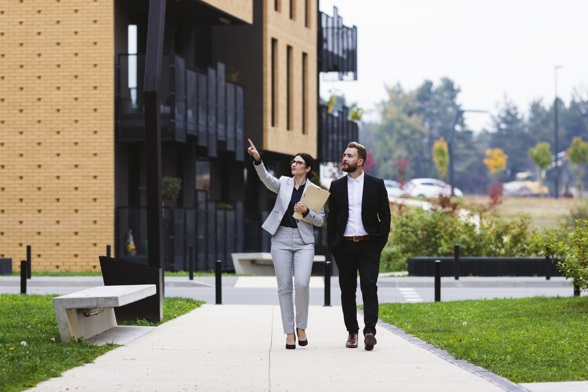 photo of man and woman pointing to building