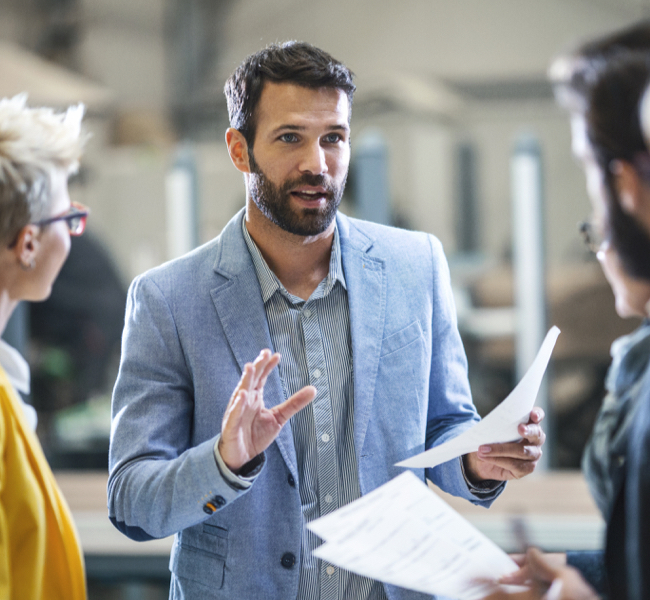 Man looking at group of people with papers in hand