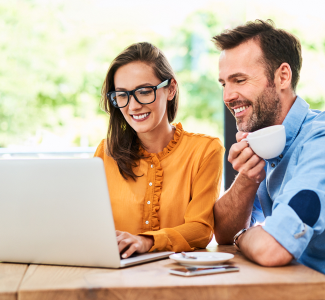 Woman and man smiling as they work on laptop