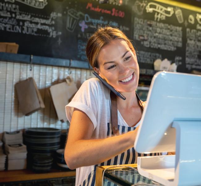 Women barista at checkout computer smiling