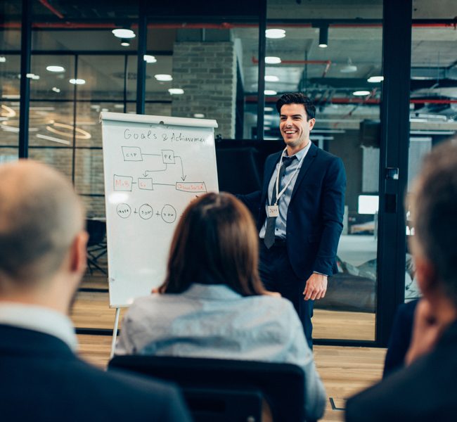 Man giving presentation in front of colleagues smiling