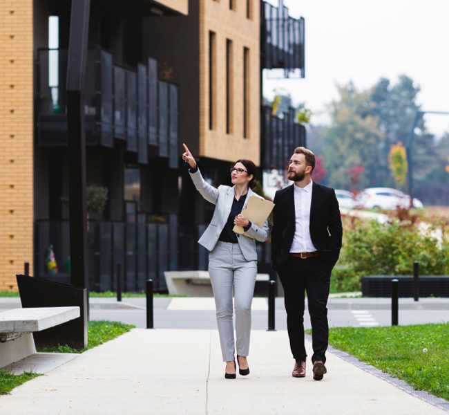 woman and man walking pointing at buildings