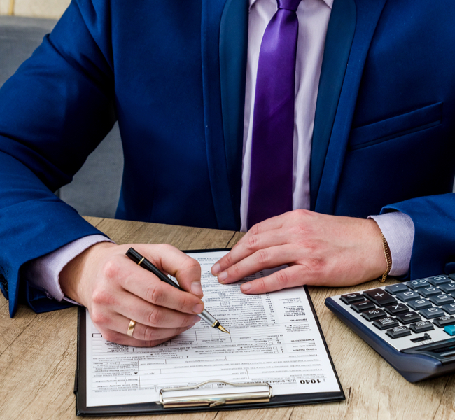 man in blue suit and purple shirt signing paper on desk